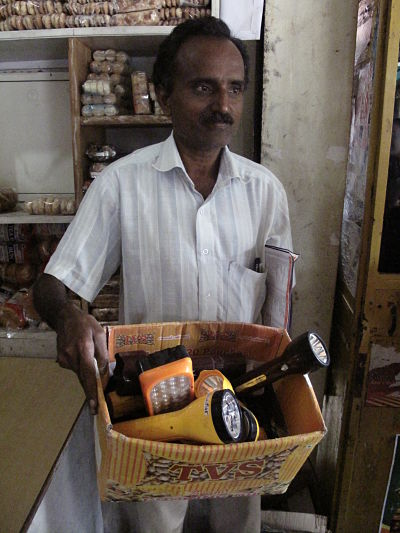 Store owner Subramania keeps a box of the broken flashlights used by most people in rural Pollachi. Essmart's solar lamps and flashlights come with a one-year warranty and are becoming more popular with his customers. (Credit: Rhitu Chatterjee)